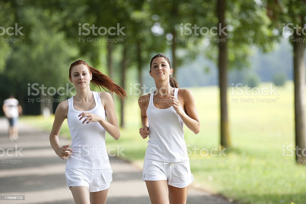 two young woman running in a park stock photo