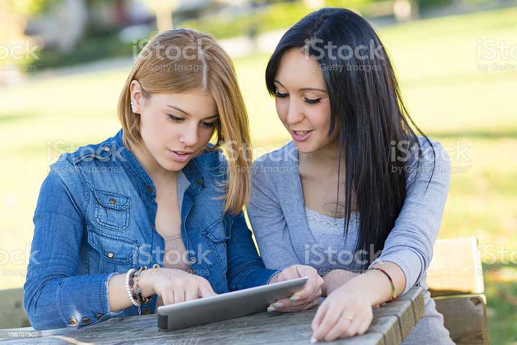 Two young woman smiling using a tablet royalty-free stock photo