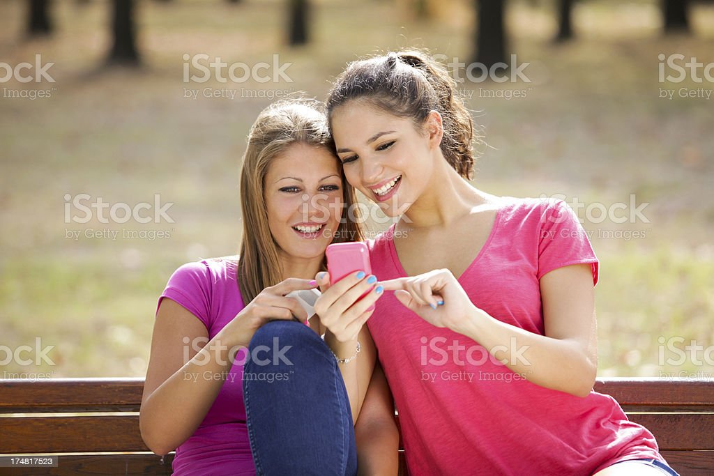 Two young woman with mobile phone stock photo