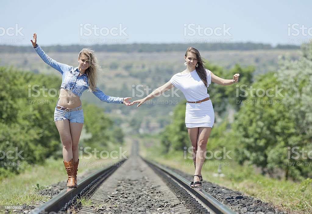 Two young women are walking along railway royalty-free stock photo