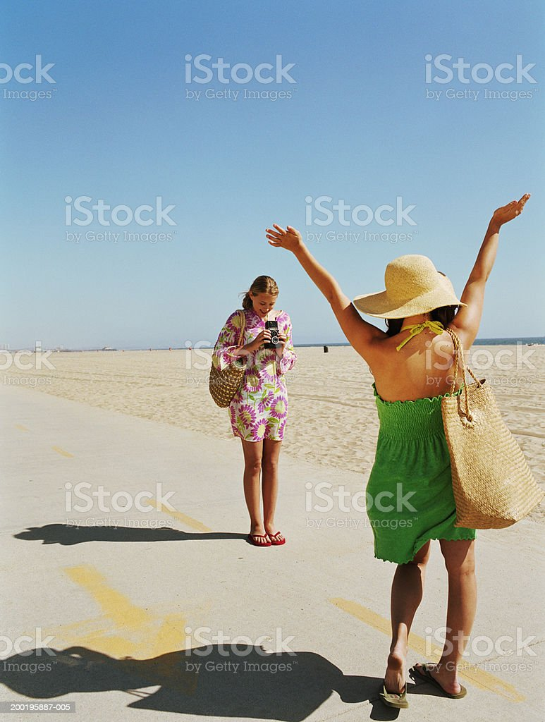 Two young women at beach, one taking photo of other stock photo