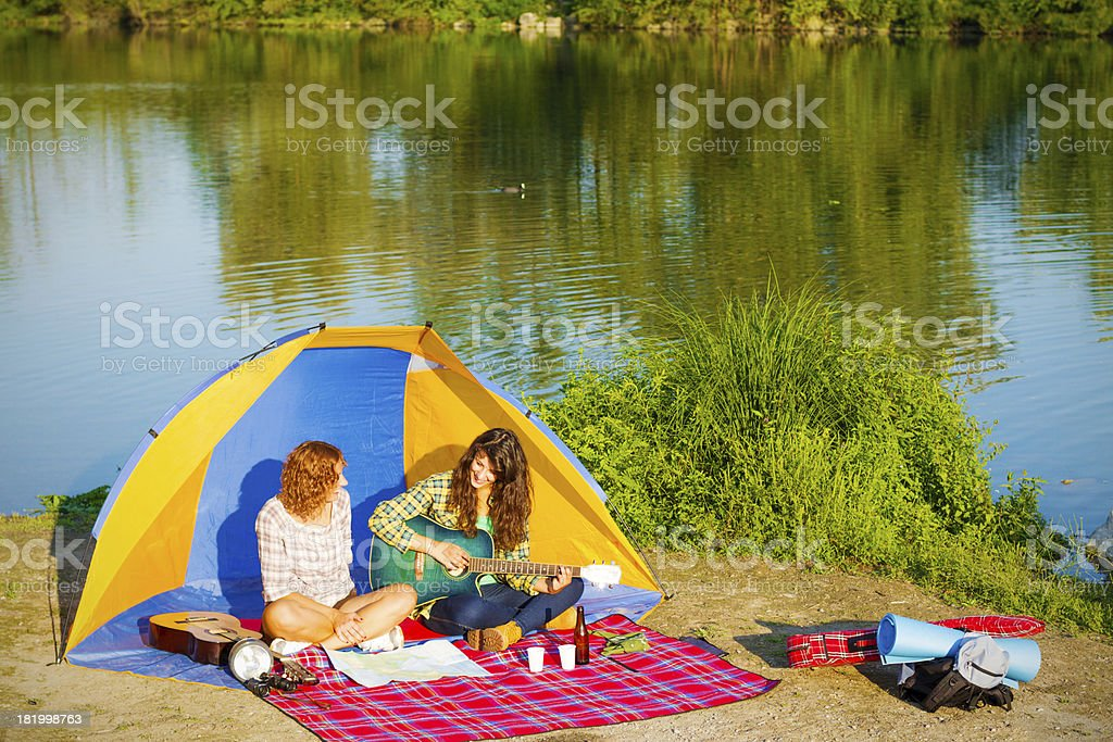 Two young women camping at river royalty-free stock photo
