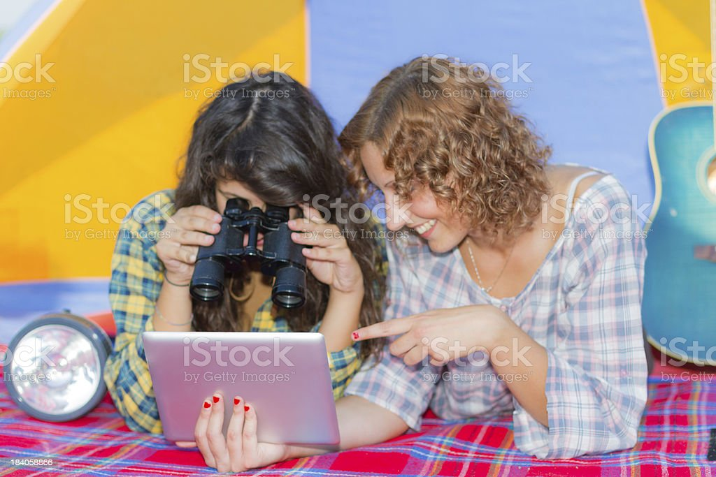 Two young women camping at river reading on digital tablet royalty-free stock photo