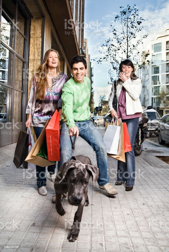 Two Young Women Carrying Shopping Bags and Man Walking Dog royalty-free stock photo