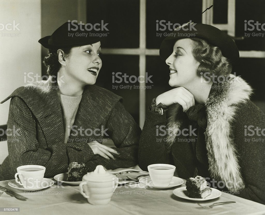 Two young women chatting, having coffee and cake, (B&W) stock photo