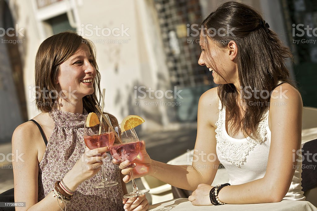 Two Young Women Cheering with Cold Drinks royalty-free stock photo
