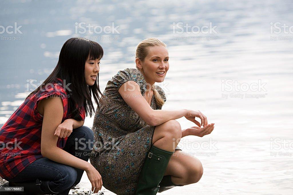 Two young women crouching near lake royalty-free stock photo