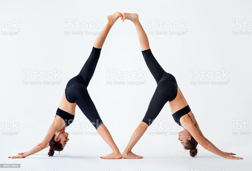 Two young women doing partner yoga asana downward facing dog stock photo