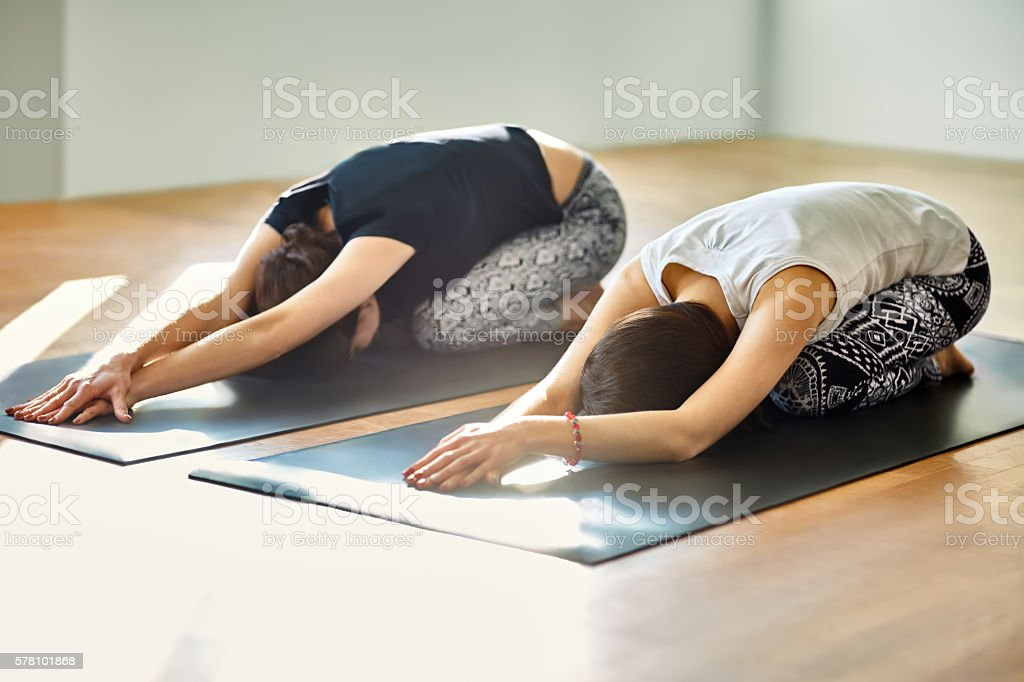 Two young women doing yoga asana child's pose stock photo
