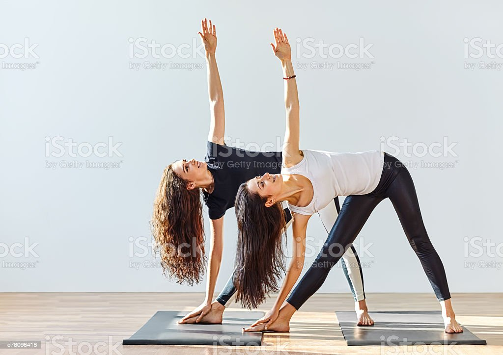 Two young women doing yoga asana extended triangle pose stock photo