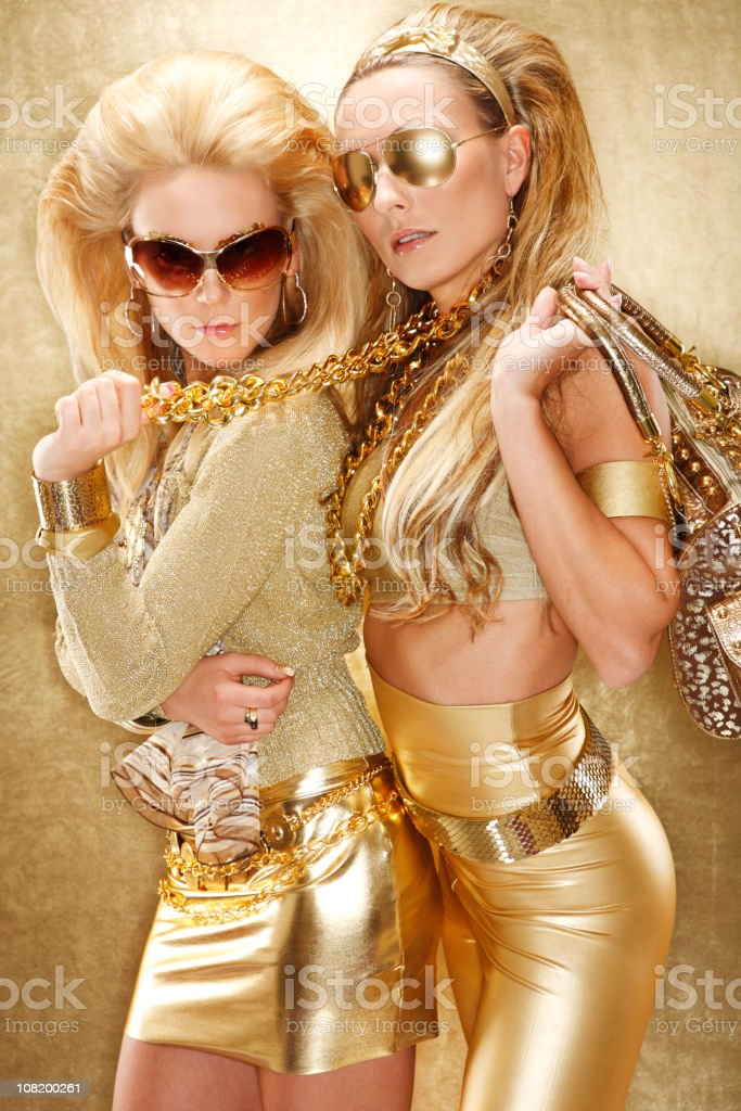 Two Young Women Dressed in All Gold Clothing Posing royalty-free stock photo