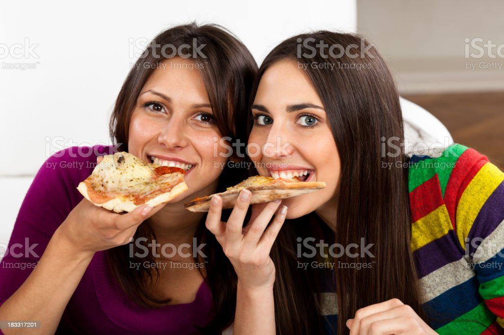 Two young women eating pizza royalty-free stock photo
