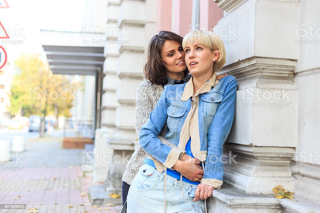 Two young women embracing and leaning back on building stock photo