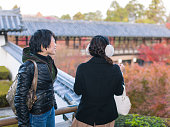 Two young women enjoy watching autumn foliage in temple, Kyoto