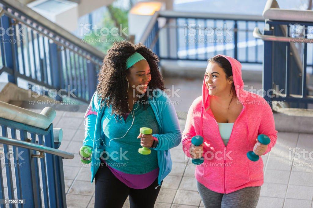 Two young women exercising, powerwalking up stairs stock photo
