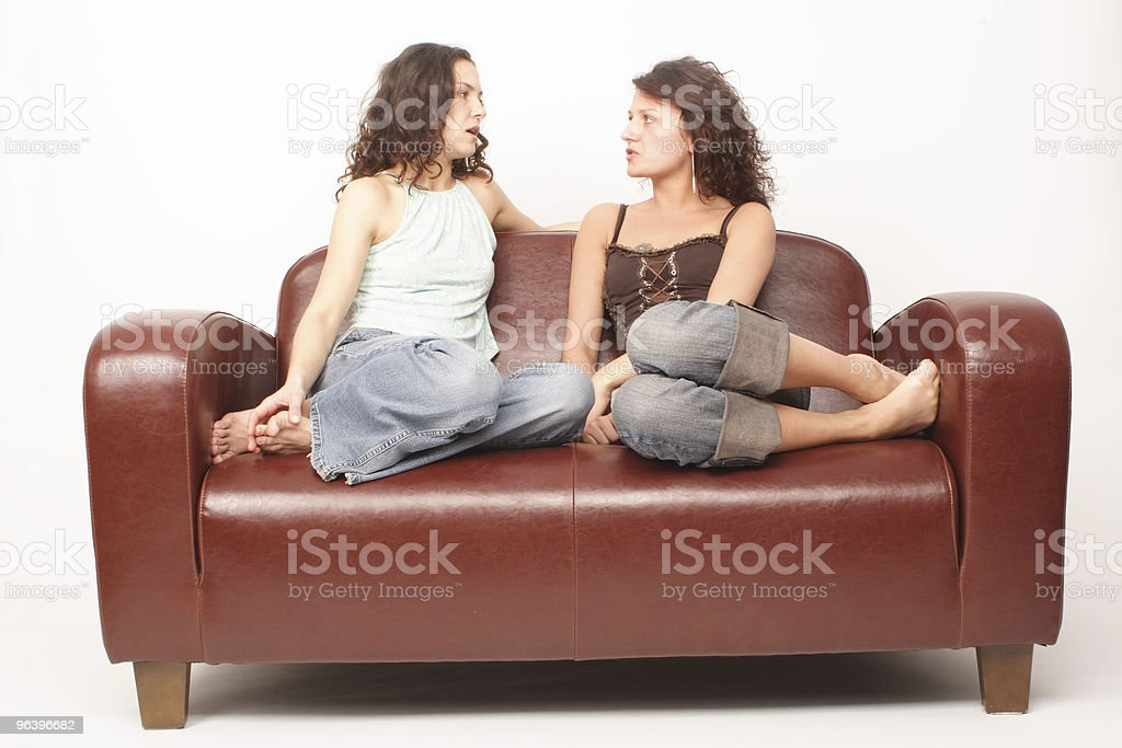 Two young women friends sitting on sofa and talking royalty-free stock photo