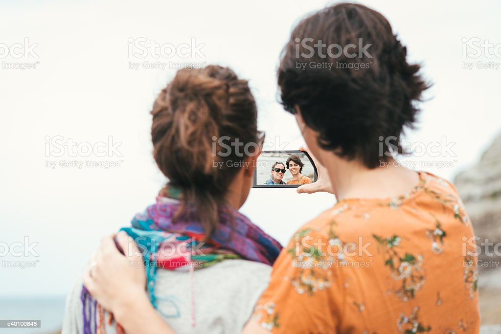Two young women friends taking a selfie by the sea stock photo