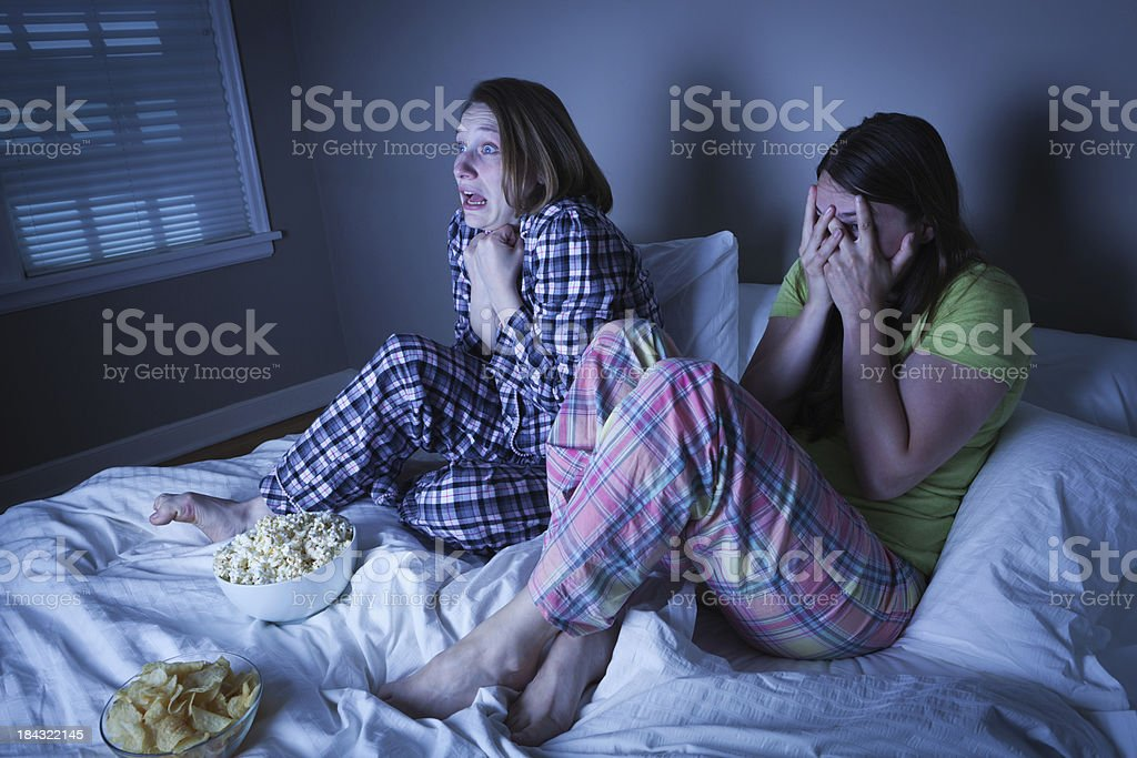 Two Young Women Friends Watching Thriller Scary Movie in Bed royalty-free stock photo