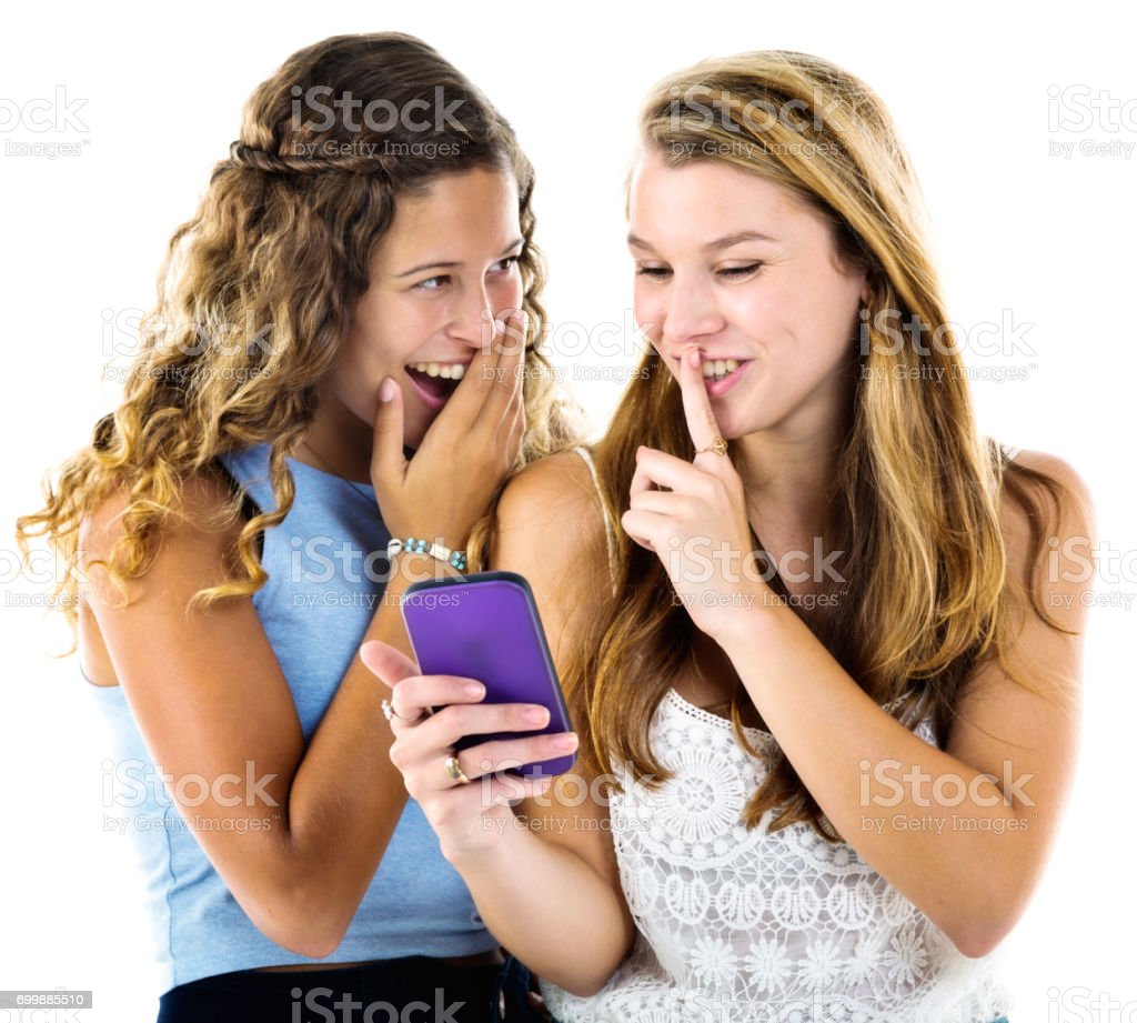 Two young women giggle together over mobile phone stock photo