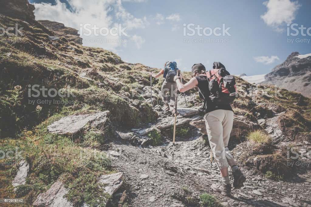 Two Young Women Hiking in Direction of Mountain Summit stock photo