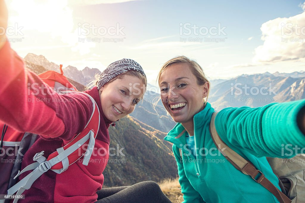 Two young women hiking take selfie portrait at mountain top stock photo
