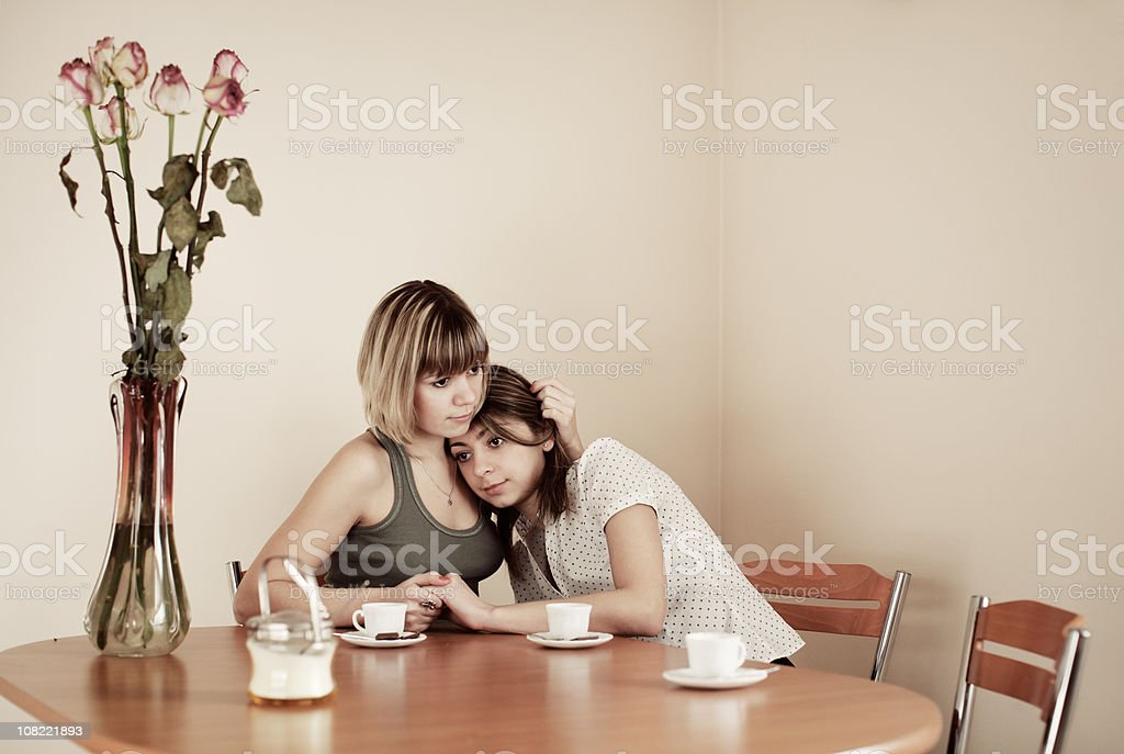 Two Young Women Hold Each Other at Kitchen Table royalty-free stock photo