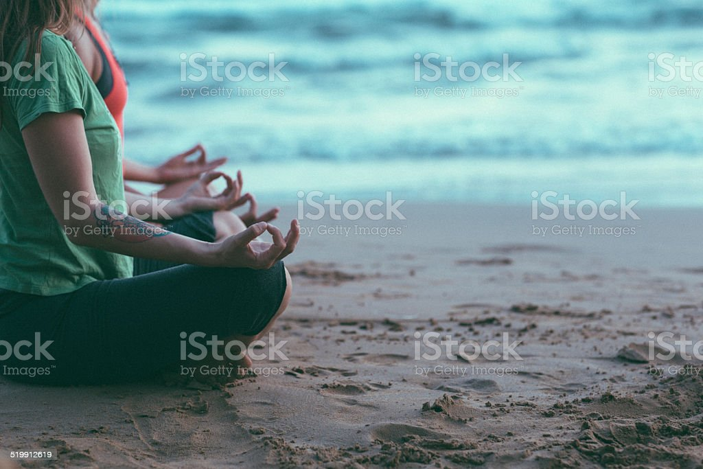 Two young women holding an aum hand position stock photo