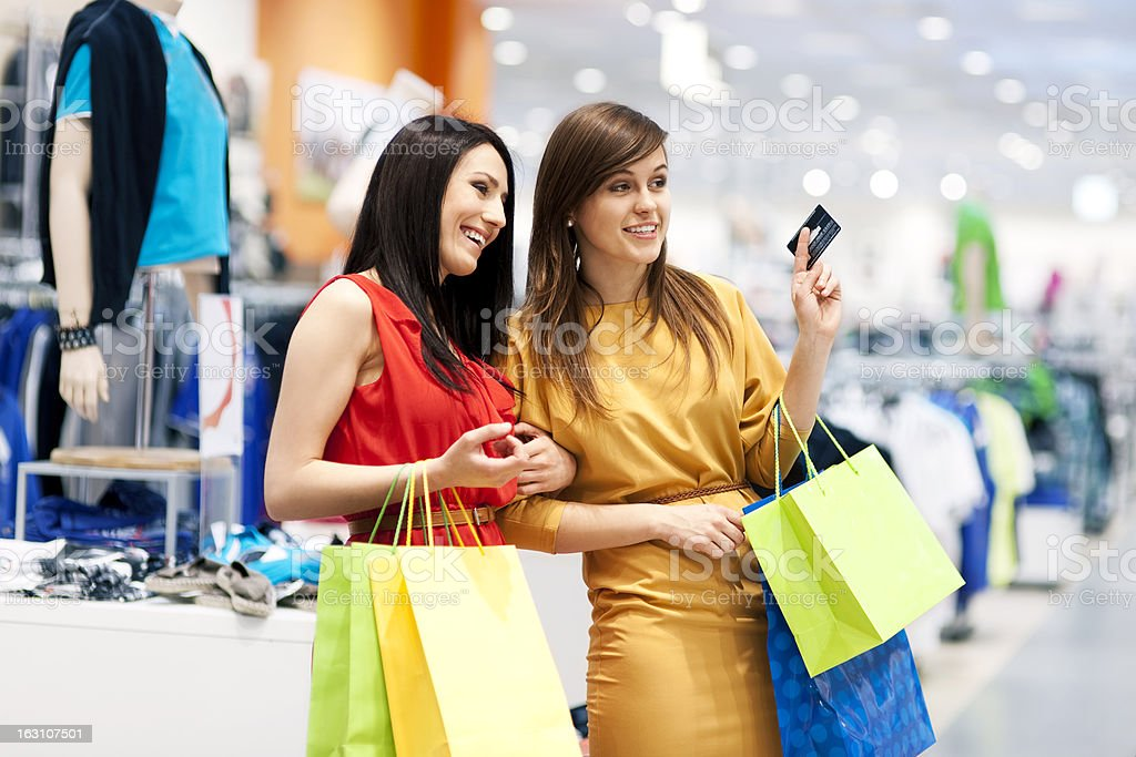Two young women holding shopping bags in department store stock photo
