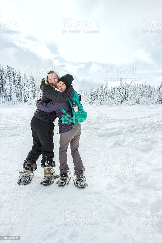 Two Young Women Hugging and Smiling While Back Country Snowshoeing stock photo