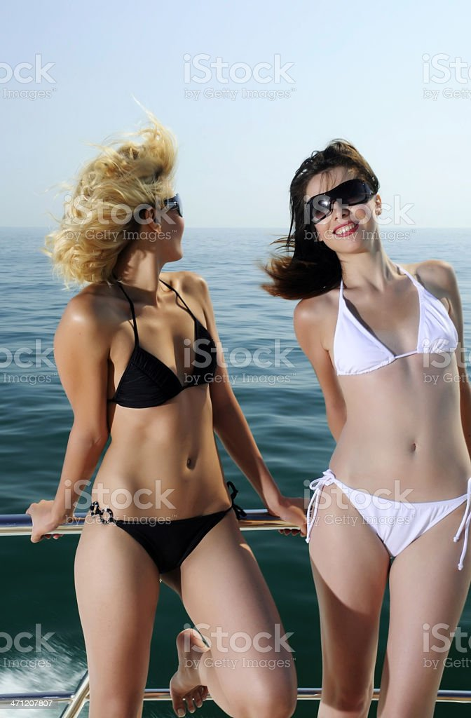 Two Young Women in Bikini's Leaning on Railing of Boat royalty-free stock photo
