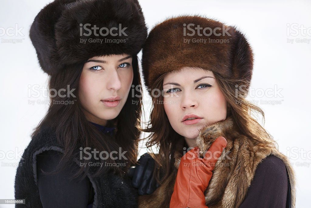 Two young women in fur hats at winter forest royalty-free stock photo
