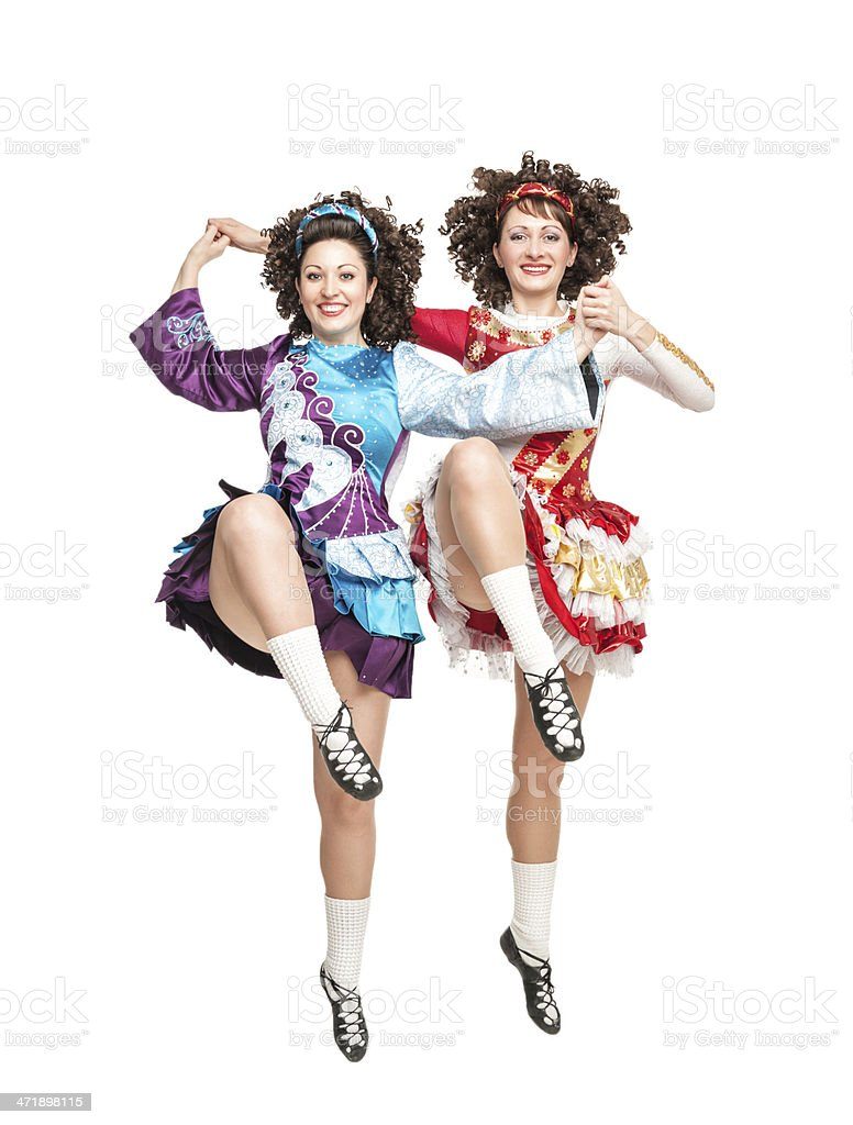 Two young women in irish dance dress dancing isolated stock photo