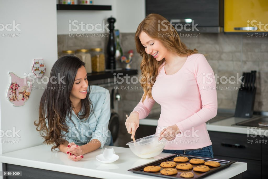 Two young women in kitchen baking chocolate chip cookies stock photo