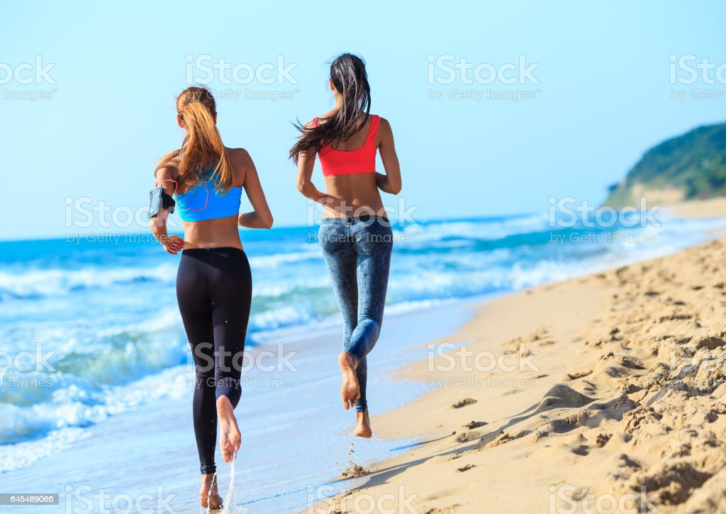 Two young women jogging on coastline stock photo
