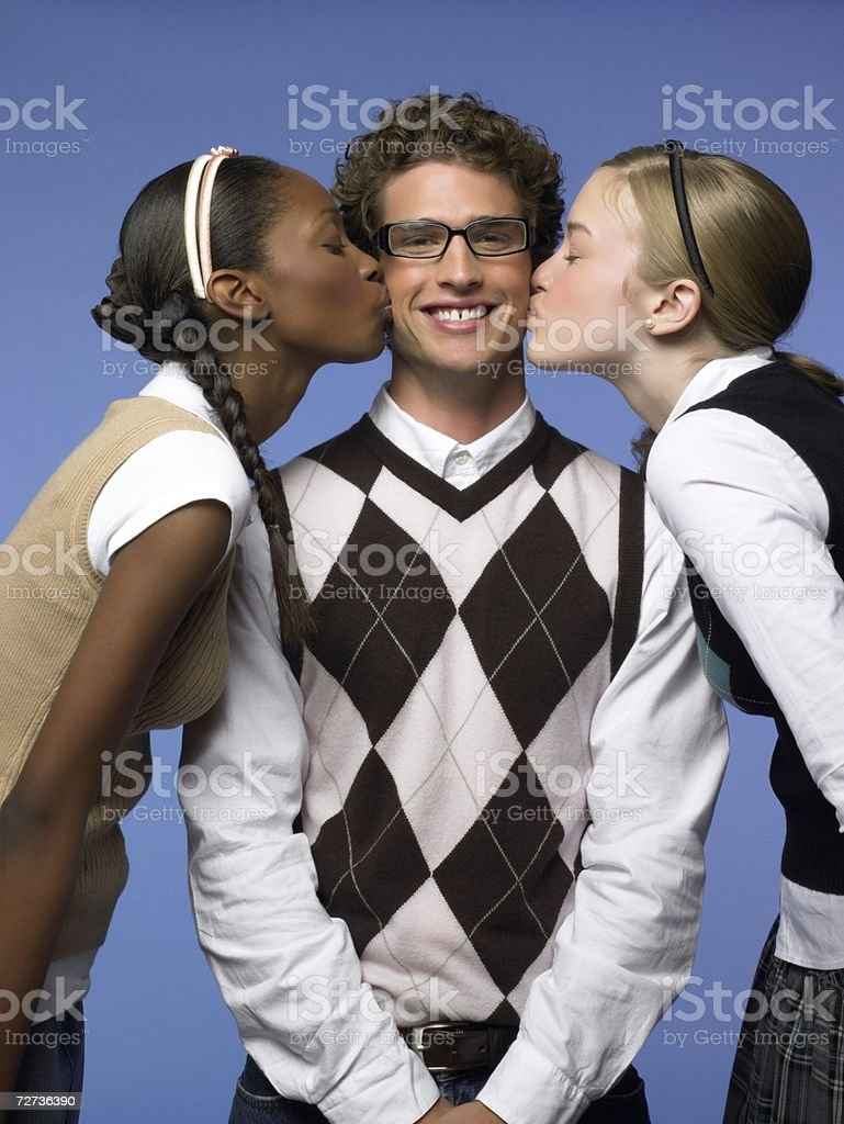 Two young women kissing a man stock photo