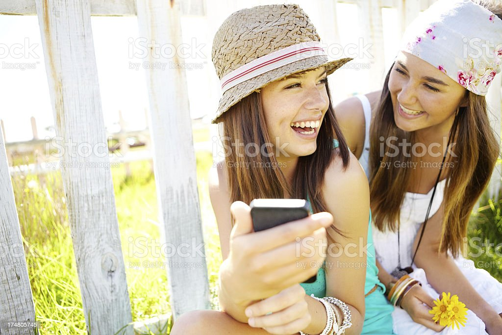 Two young women laughing at content in phone stock photo