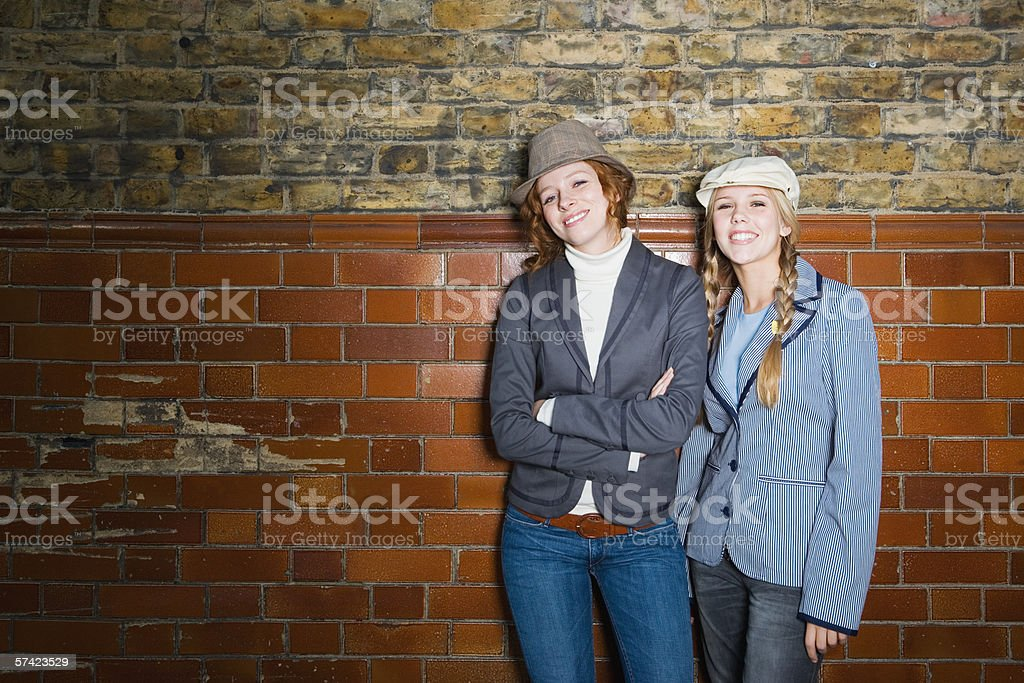 Two young women leaning against wall stock photo