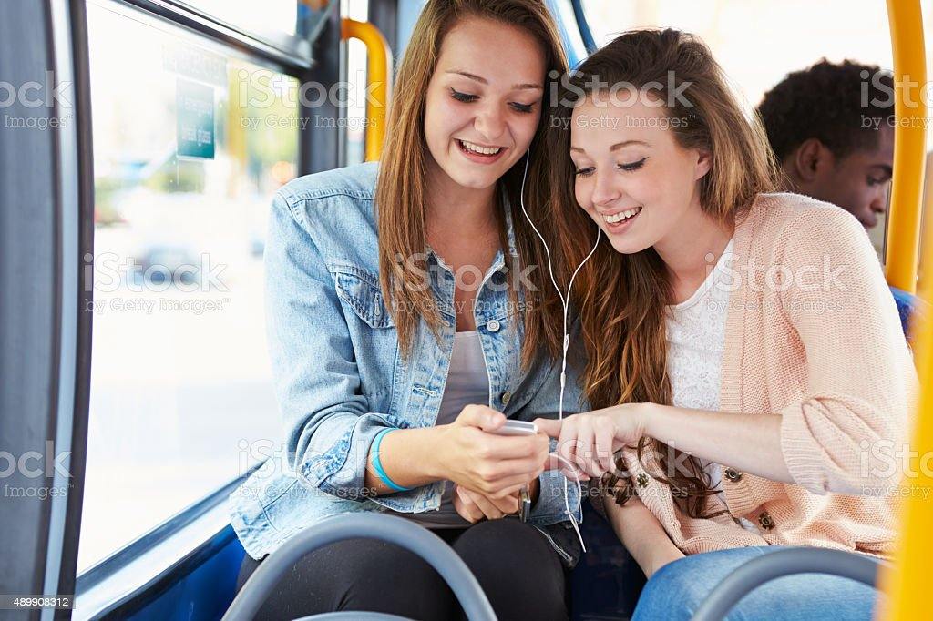 Two Young Women Listening To Music On Bus stock photo