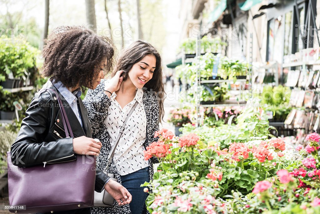 Two young women looking at flowers and smiling stock photo