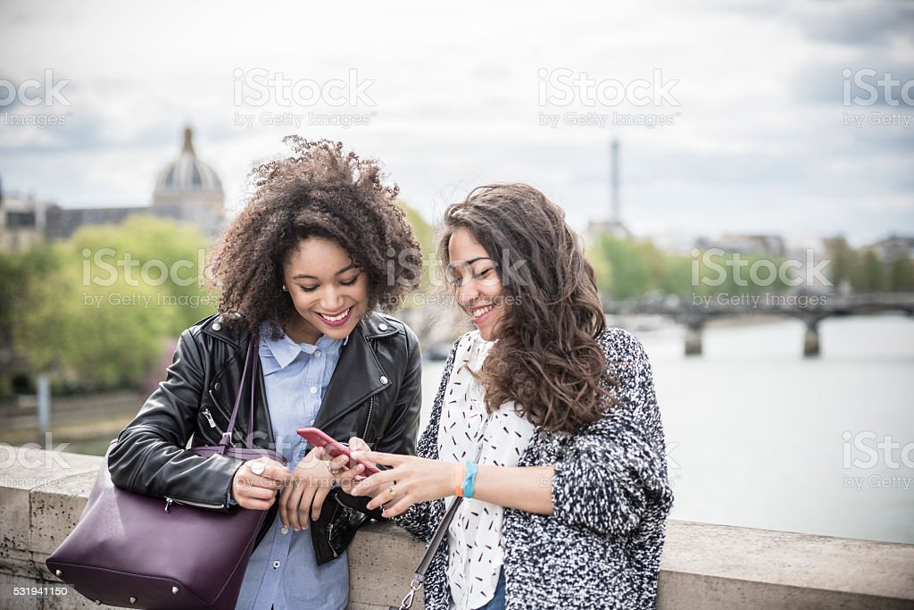 Two young women looking at mobile phone togteher stock photo