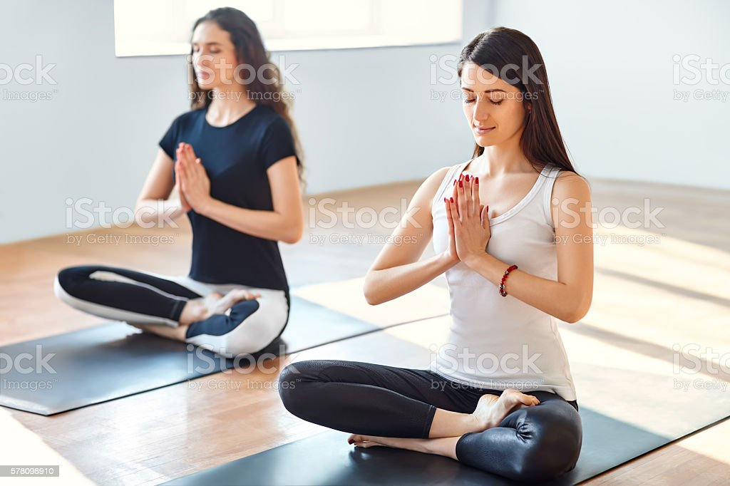 Two young women meditating in lotus pose stock photo