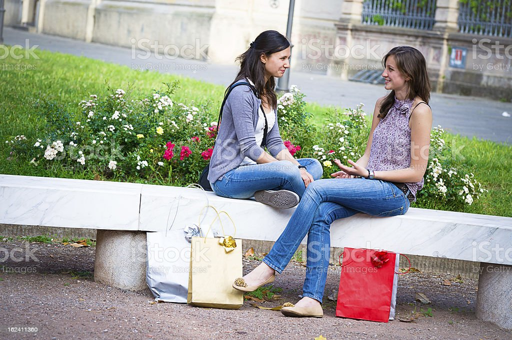 Two Young Women on a Bench at Park royalty-free stock photo