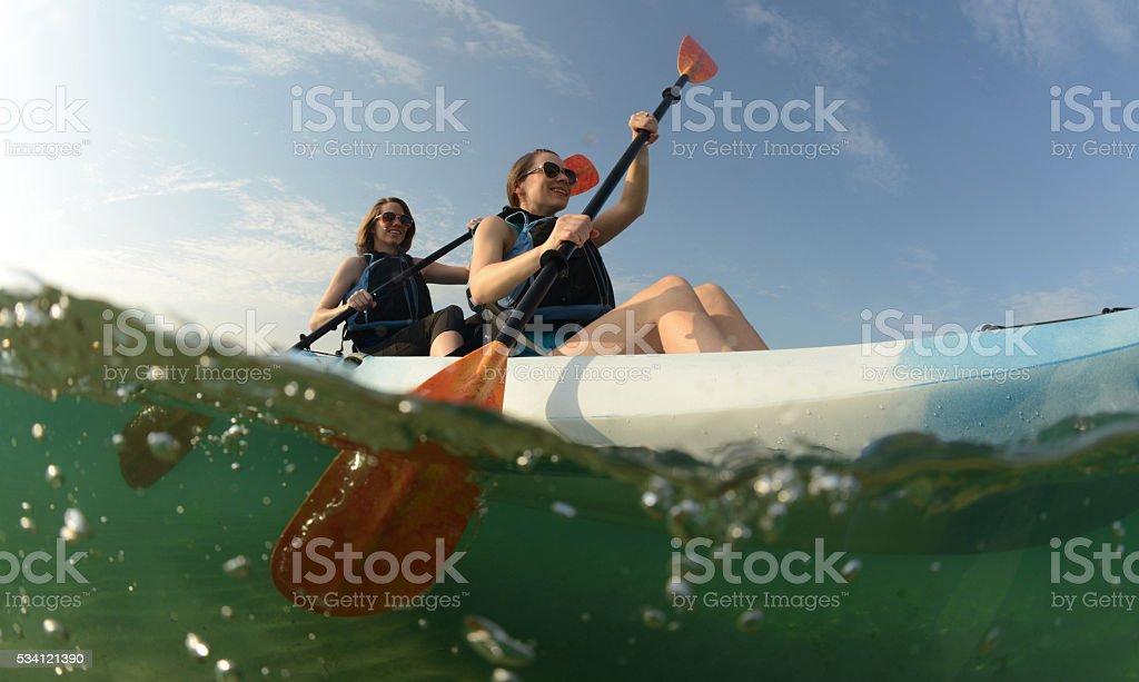 Two young women paddling blue kayak stock photo