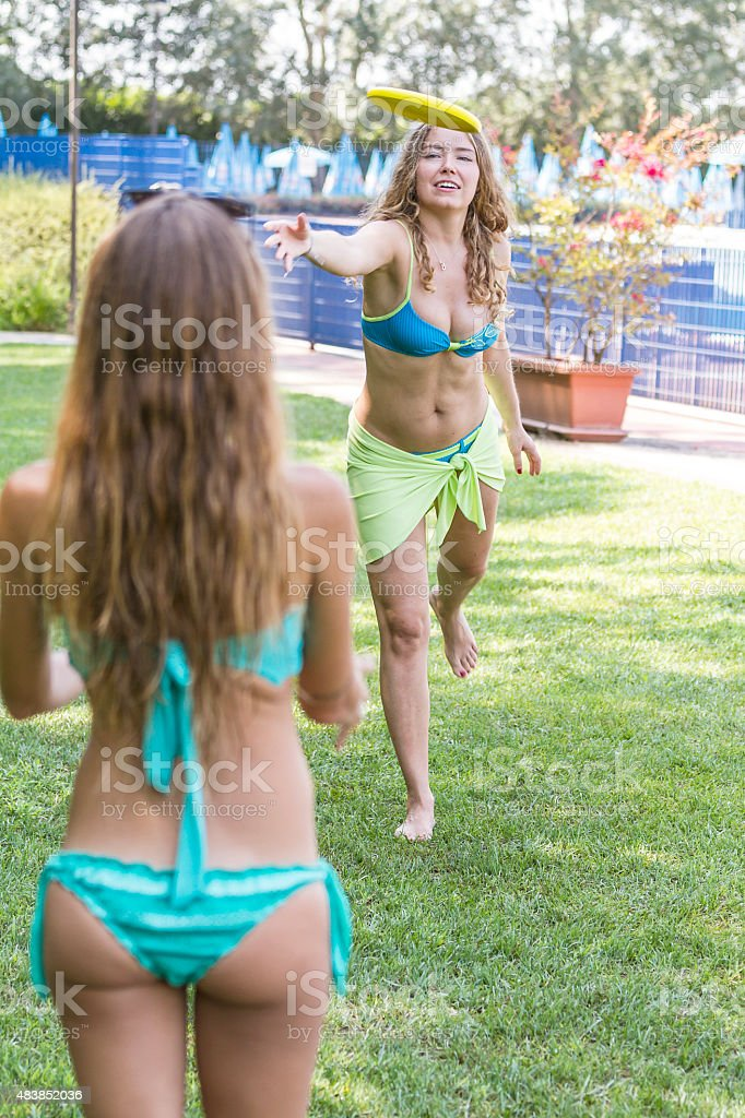 Two young women playing frisbee stock photo