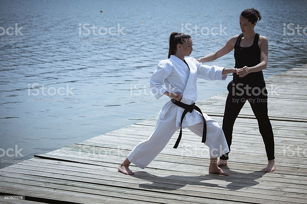 Two young women practising karate outdoors stock photo