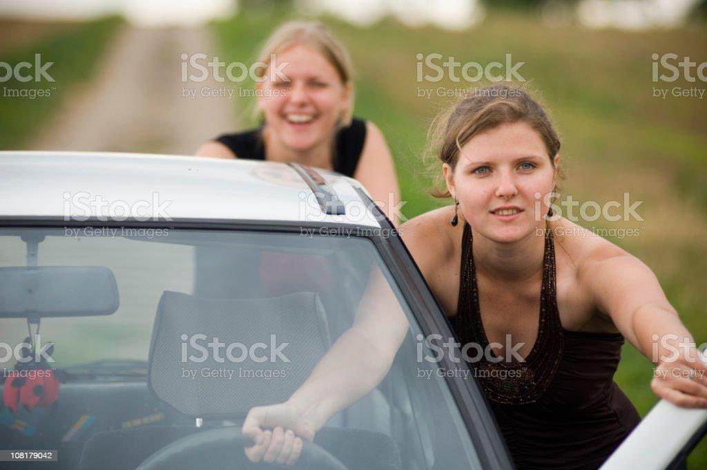 Two Young Women Pushing Car Down Road stock photo