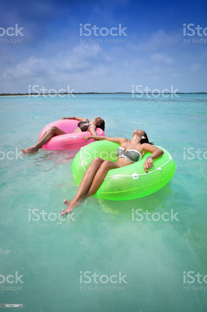 Two young women relaxing with tubes in a Tropical beach royalty-free stock photo