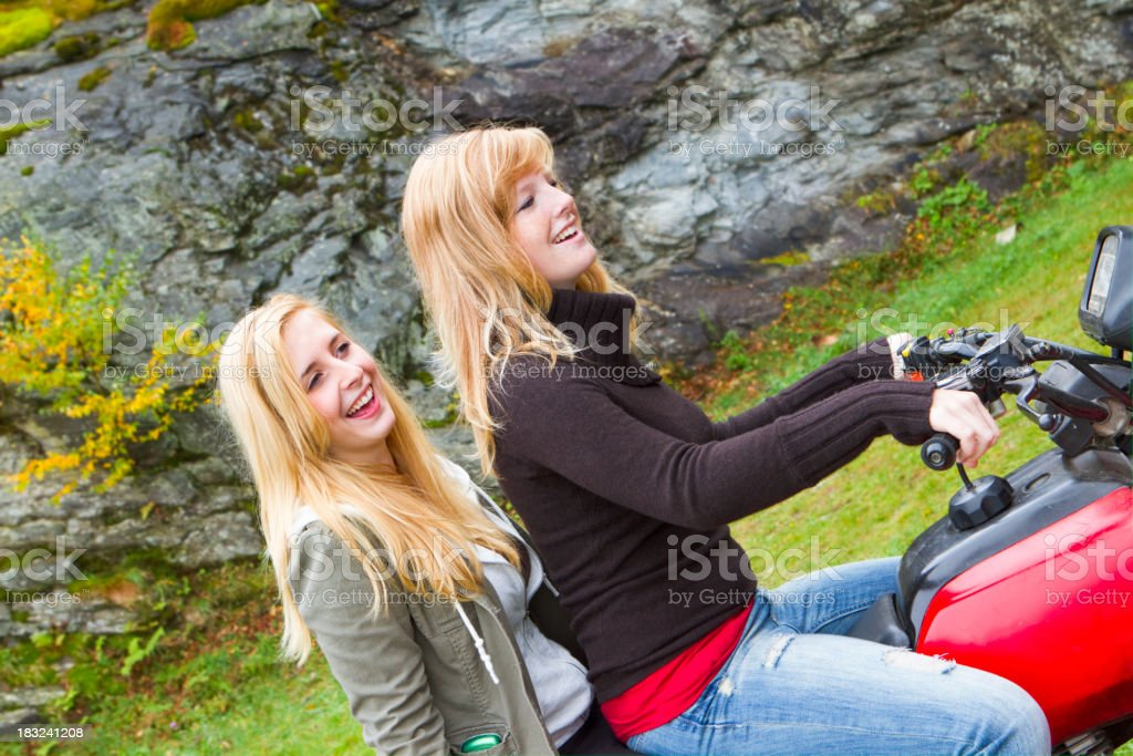 Two Young Women Riding A Four-wheeler In The Mountains stock photo