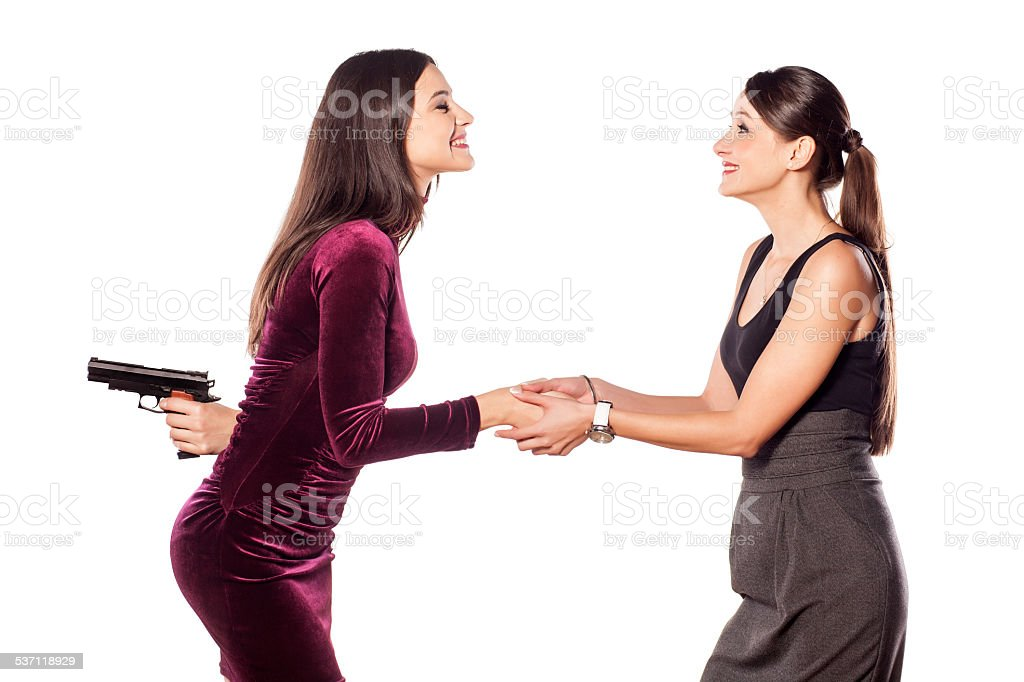 Two young women shake hands warmly with gun behind stock photo