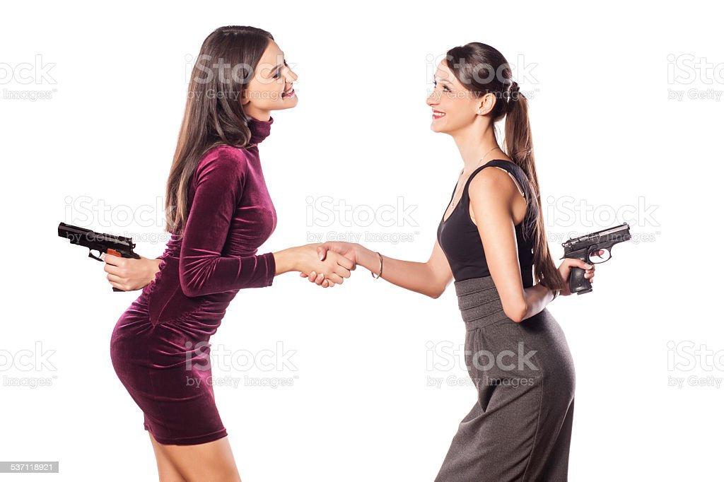 Two young women shake hands warmly with guns behind stock photo